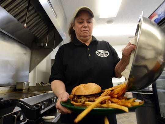 Diane Deitrick, owner of The Stagecoach Restaurant on Main Street in Duncan Falls, puts the finishing touches on a Stagecoach burger, the restaurant's signature dish.