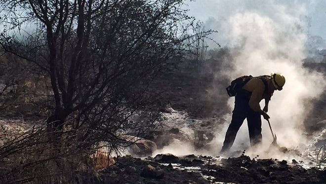 A firefighter works earlier during the Rey Fire. The situation has changed, with the  blaze 96 percent contained Thursday.