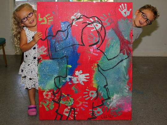 Lola and Leo Grabinski with the artwork they created for the 2017 Southwest Florida Wine & Food Fest.