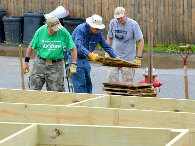 Volunteers Jimmy Owens, Alan Biskey and Tom Kelley work together to place raised gardening beds, making sure they are level, within the Burress Community Garden off Heydenreich Street in Staunton on Wednesday, May 14, 2014.