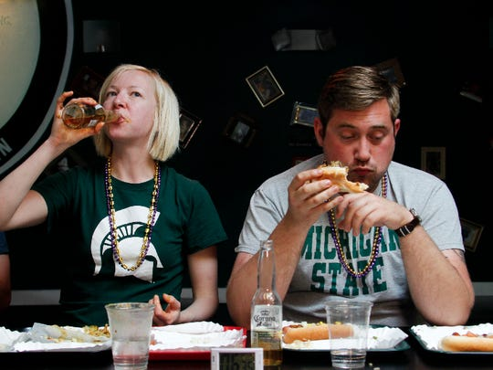 Meredith Boxberger washes down her ninth hot dog with a swig of beer next to fellow MSU graduate student Derek McBaine on Tuesday at What Up Dawg? in East Lansing. Boxberger finished all nine signature dogs in about 13:30. McBaine couldn't finish the 20-minute challenge, leaving a little less than two hot dogs on his tray.