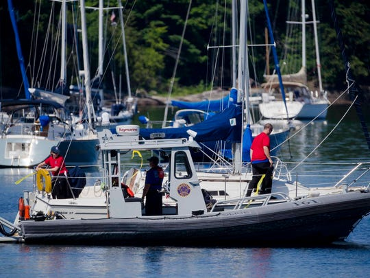 Crew members on a Colchester Police Department boat tape off missing boater Brian Webb's sailboat during a search for him Monday on Malletts Bay Monday.