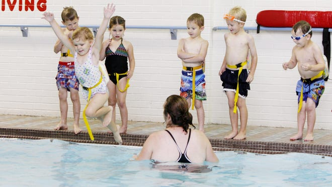 A preschooler leaps into the pool at the YMCA while the other children wait their turn during a swim class taught at the Y.