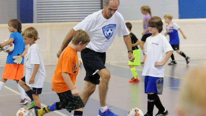 Bobby McAvan dribbles the ball away from a young player during warmups at Northside Park in Ocean City during McAvan's For The Love Of Soccer camp.