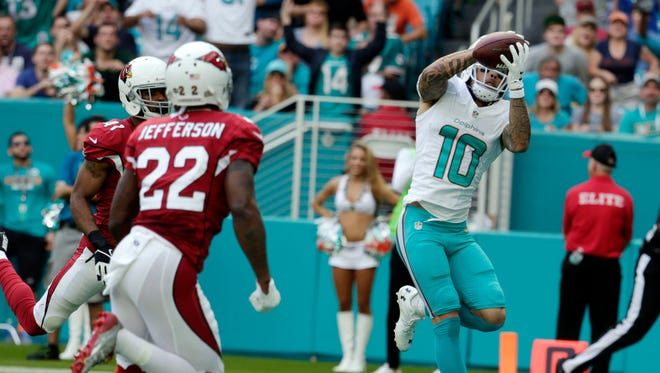 Miami Dolphins wide receiver Kenny Stills (10) catches a pass in the end zone for a touchdown as Arizona Cardinals strong safety Tony Jefferson (22) and cornerback Marcus Cooper (41) are late with the tackle, during the first half of an NFL football game, Sunday, Dec. 11, 2016, in Miami Gardens, Fla.