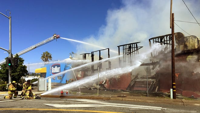 Firefighters use water hoses and a ladder truck to put out a Saturday afternoon fire in a building next to Bedmart at Wyndham Lane and South Market Street.