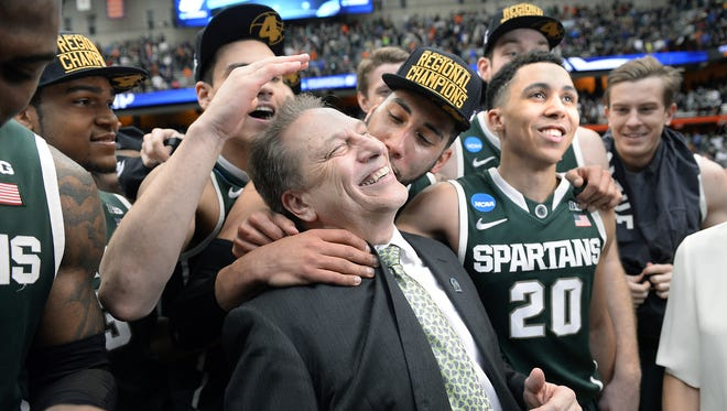 MSU head coach Tom Izzo gets a hug from player Denzel Valentine, center, with players Gavin Schilling, left, and Travis Trice, right, after MSU's 76-70 win over Louisville in their NCAA Elite Eight  game in Syracuse, NY Sunday 3/29/2015. MSU now heads to Indianapolis for the Final Four.