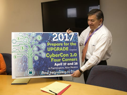 San Juan College Center for Workforce Development Director Lorenzo Reyes displays a sign promoting the center's April cybersecurity conference during a meeting on Tuesday.