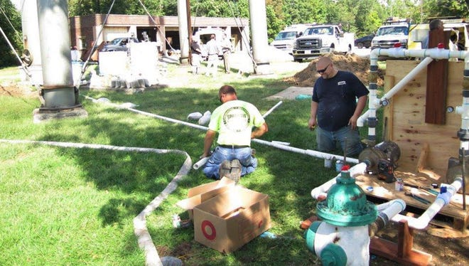 In this September 10, 2015 photo, contractors assemble pipes to flush out a fire hydrant beneath the water tower at the state veterans home in Quincy, Ill. The homeís drinking water system was disinfected with chlorine to help fight a Legionnairesí disease outbreak that has killed nine residents so far and sickened at least 45 other people at the home, including five workers.