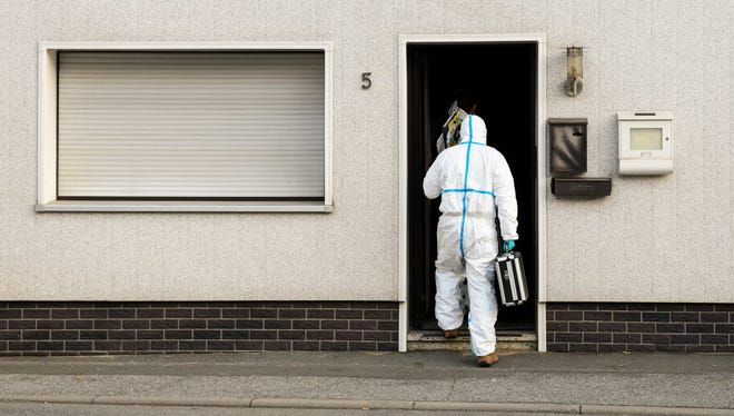 A police investigator in protective cloth enter a house in Wallenfels, southern Germany on Nov. 13 where police found bodies of multiple babies.