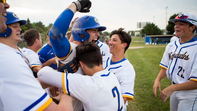 Germantown's Joe Seymour is swarmed by teammates after he drives in the winning run in a 5-4 victory over Nicolet in a WIAA regional final Wednesday at Germantown..
