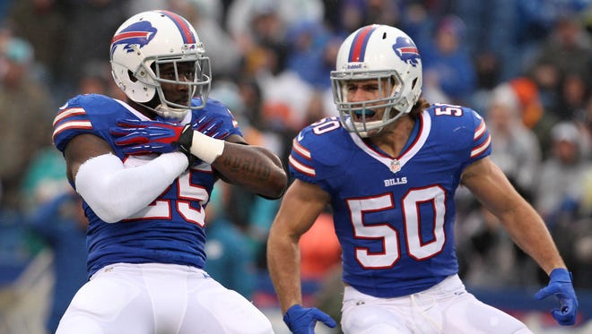 Buffalo Bills strong safety Da'Norris Searcy (25) celebrates his sack with teammate middle linebacker Kiko Alonso (50) during the first quarter against the Miami Dolphins at Ralph Wilson Stadium.