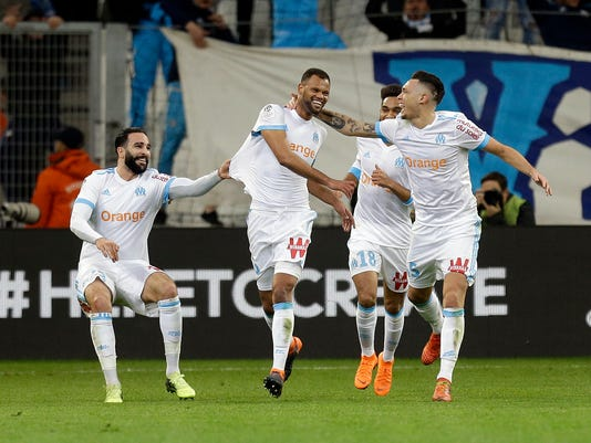 Marseille's Rolando Da Fonseca, center, celebrates with teammates Adil Rami, left, and Lucas Ocampos after scoring, during the League One soccer match between Marseille and Lyon at the Velodrome stadium, in marseille, southern France , Sunday, March 18, 2018. (AP Photo/Claude Paris)