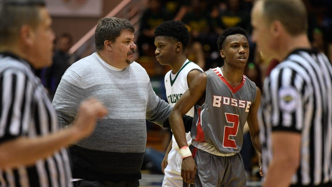 Bosse head coach Shane Burkart helps Mekhi Lairy off the court in the fourth quarter as the Evansville Bosse plays Crispus Attucks in the Boys' Semi-State Basketball Tourney at Seymour High School Saturday, March 18, 2017.