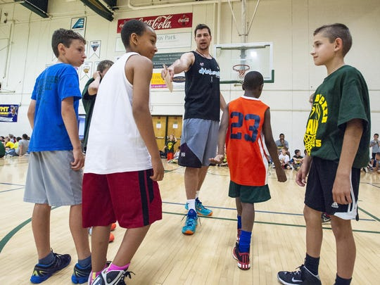 Former University of Vermont basketball player Chris Holm sets up a drill during a basketball camp hosted by coach John Becker at Patrick Gymnasium in Burlington on Friday.