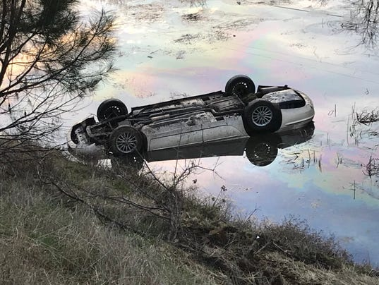 Car upside down in pond