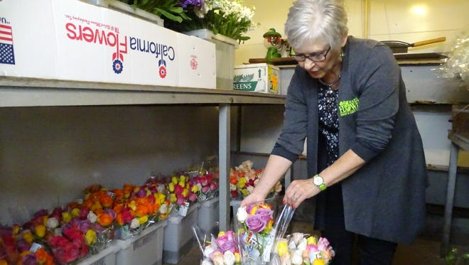 Judi Noblit, who works for Marion Flower Shop, shows that less than 10 crates of roses remained about two hours after the store opened Wednesday to distribute roses for the Good Neighbor Day.