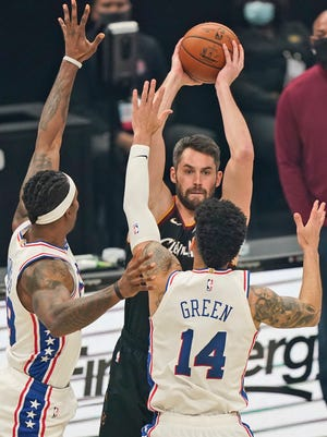 Cleveland Cavaliers' Kevin Love, back, tries to pass over Philadelphia 76ers' Dwight Howard, left, and Danny Green in the first half of an NBA basketball game, Sunday, Dec. 27, 2020, in Cleveland. (AP Photo/Tony Dejak)