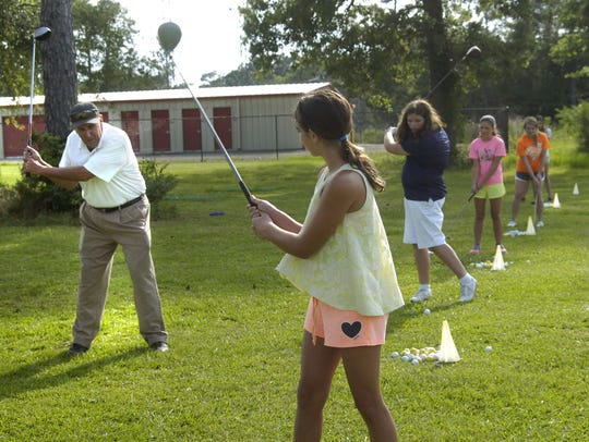 Lou Dechert (left) teaches a girls golf class in 2014.
