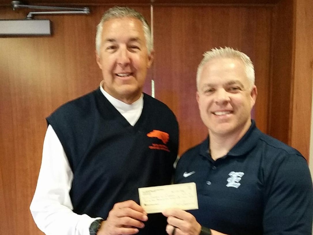 Enka boys basketball coach Brian Carver, right, presents a check to N.C. Basketball Coaches Association treasurer Gary Bowne from last year's Coaches vs. Cancer Shootout in Asheville.
