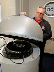 Project GRILL chairperson Scott Kuehn lifts the lid
