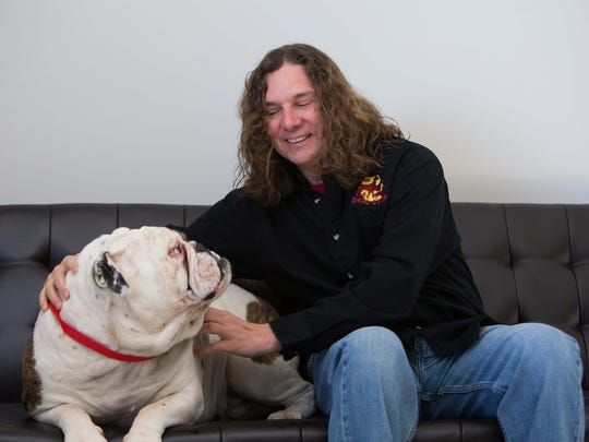 Jim Henry, owner of The Dog Stop, sits with Sid at the second Delaware location in Middletown.