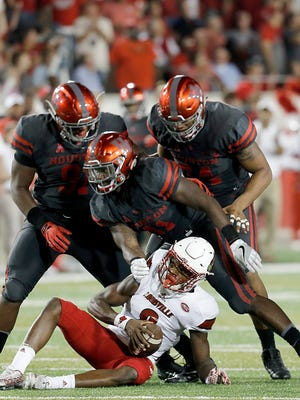 Quarterback Lamar Jackson of the Louisville Cardinals is sacked by linebacker Steven Taylor of the Houston Cougars.
