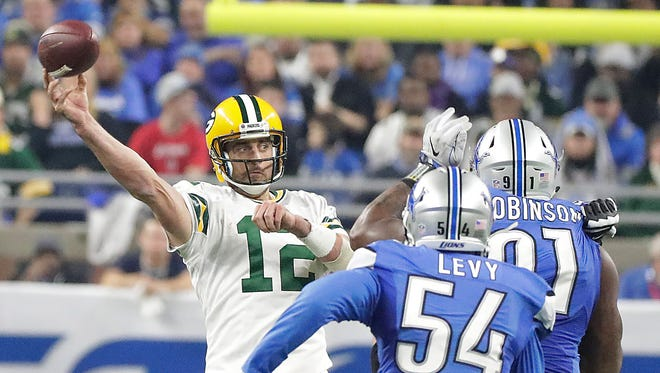 Green Bay Packers quarterback Aaron Rodgers (12) throws under pressure against the Detroit Lions at Ford Field.