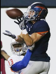 UTEP receiver Cole Freytag leaps over Houston Baptist defender Derek Broussard to make a touchdown catch Saturday at the Sun Bowl.