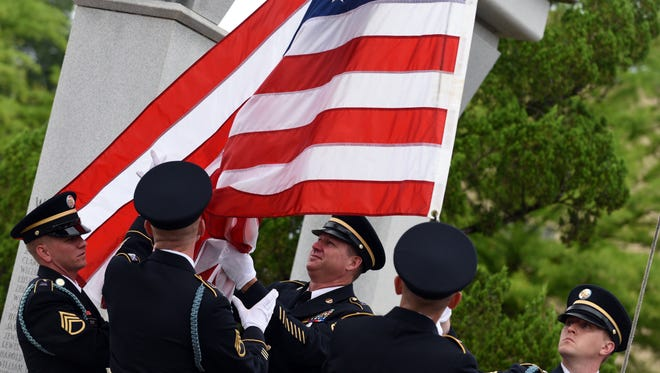 The Maneuver and Training Equipment Support of Camp Shelby take down the American flag after the Memorial Day Service held at the Veterans Memorial Park.