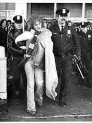 Rock concertA policeman wielding a nightstick leads away a rock fan, who was not arrested.