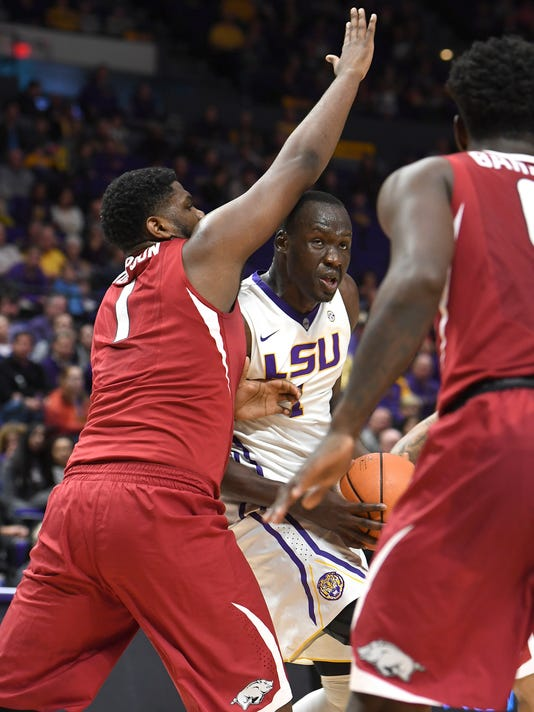 LSU's Duop Reath (1) eyes the basket while fighting off Arkansas players in the first half of an NCAA college basketball game in Baton Rouge, La., Saturday, Feb. 3, 2018. (Patrick Dennis/The Advocate via AP)