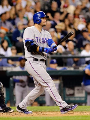 Texas Rangers catcher A.J. Pierzynski (12) hits a 3-run home run against the Seattle Mariners during the 7th inning at Safeco Field.