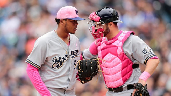 Brewers starting pitcher Freddy Peralta and catcher Manny Pina talk on the mound in the third inning.