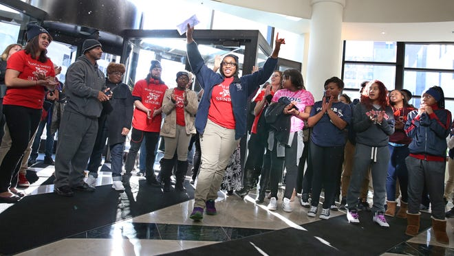 World of Inquiry School 58 senior Jada Williams raises her arms in celebration as she's called to mail her letter of intent to submit college applications at the State Supreme Court Appellate Division building in downtown Rochester on Dec. 11. The School 58 seniors and staffers took part in their traditional College March from the school to the building, where they heard remarks from college representatives.