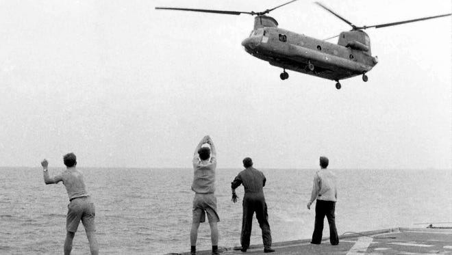 """Crew members aboard the USS Kirk signal a Chinook helicopter to hover over the deck and drop its passengers in footage used in """"Last Days in Vietnam,"""" directed and produced by Rory Kennedy."""