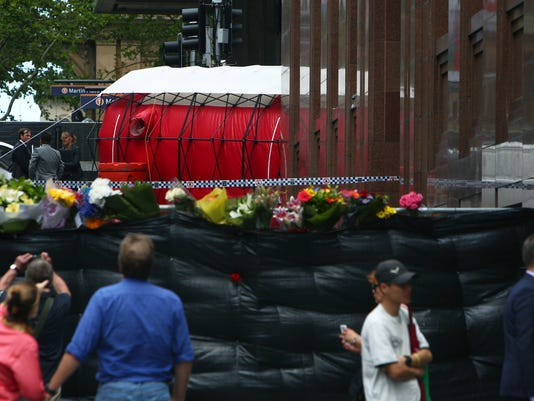 A red tent is set up at the entrance of the Lindt near a makeshift memorial at Martin Place in the central business district of Sydney Australia, Tuesday Dec. 16,  2014. Three people including a lone gunman who took siege in a Sydney CBD cafe are dead after a police action ended in the early ours of the morning. (AP/Photo/Steve Christo)