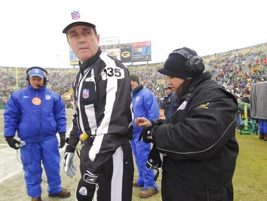 Barb Kowalczyk helps referee Pete Morelli get his wireless