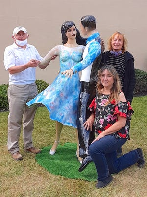 """Mayor Peter Vogt and Livingston County Economic Development downtown coordinator Louise Wadsworth celebrate the unveiling of """"Imagine...Beneath the Stars"""" with artist Deb McAfee (kneeling)."""