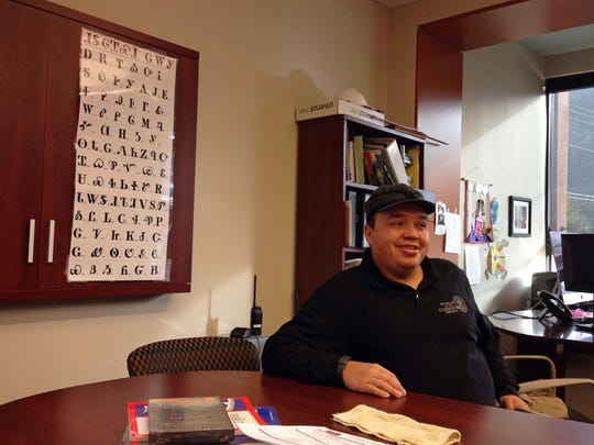 Bo Taylor sits in front of a chart showing the Cherokee alphabet at the New Kituwah Academy in Cherokee. Taylor, a tribe member, has two children at the school. With fewer than 300 native Cherokee speakers remaining in North Carolina, tribe members hope to preserve their language and culture through the small school where their children are immersed in their people's native tongue.