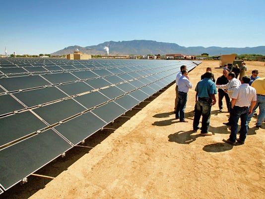 This April 2011 photo shows First Solar and Public Service Company of New Mexico officials at the  utility's photovoltaic solar array in Albuquerque.
