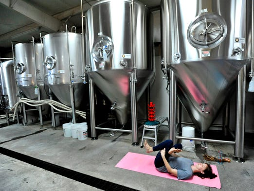 Members of Kate Townsend's yoga class at Quest Brewing Company in Greenville work through breathing and other yoga stances on Monday, August 25, 2014.