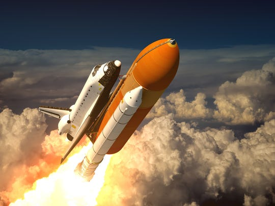 Headed into space, the space shuttle soars above a layer of clouds.