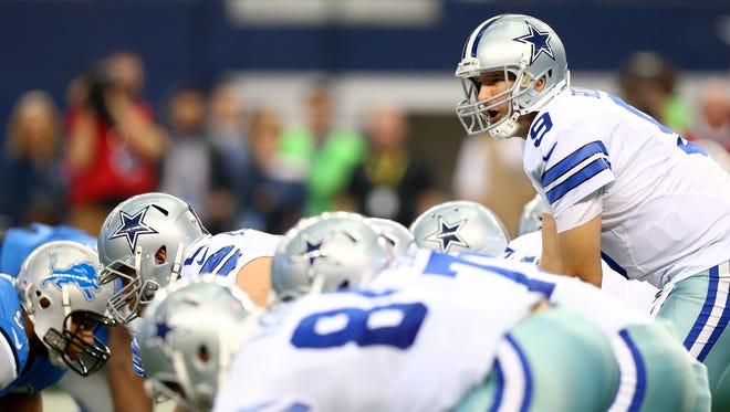 Tony Romo surveys the defense before a play against the Lions.