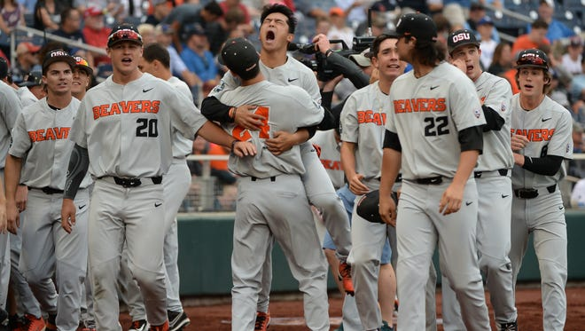 Jun 20, 2018; Omaha, NE, USA; Oregon State Beavers pitcher Nathan Burns (24) lifts center fielder Steven Kwan (4) after a home run by catcher Adley Rutschman (35) (not shown) in the first inning against the North Carolina Tar Heels in the College World Series at TD Ameritrade Park.