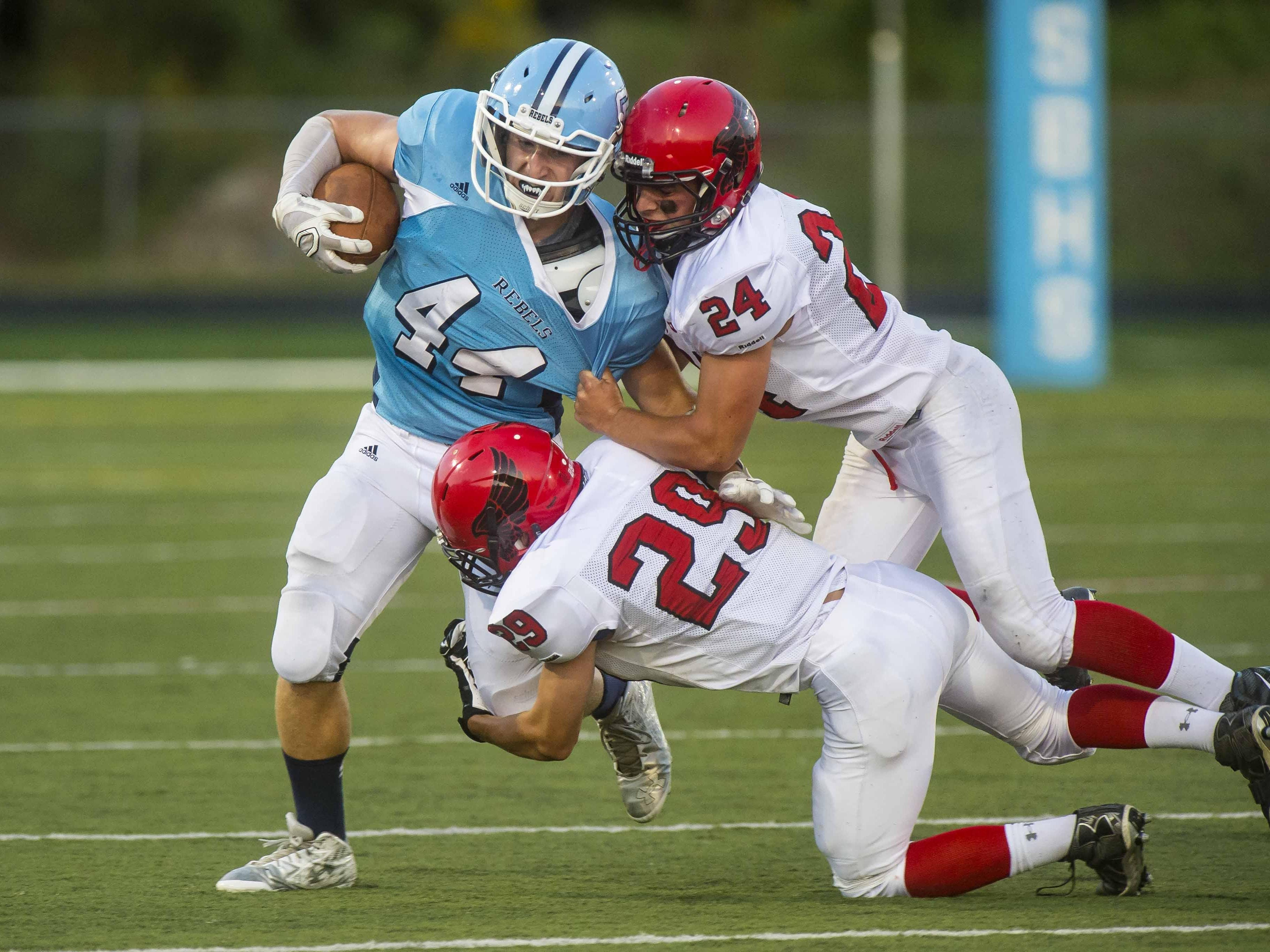 South Burlington's Jeremy Clements, left, is tackled by Champlain Valley's Nick Kinneston, top, and Braven Bose in South Burlington on Friday night.