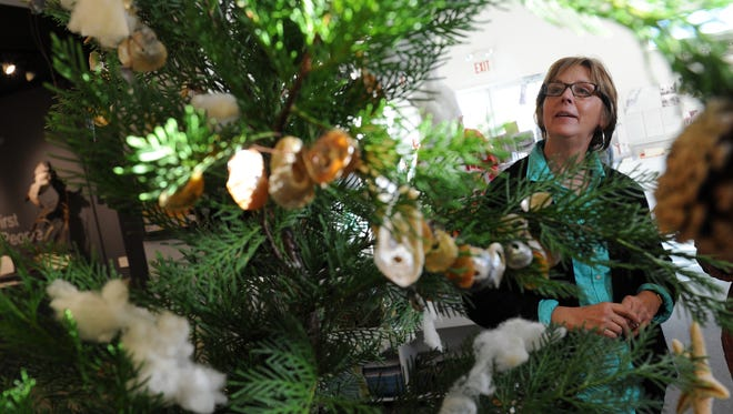 "Lisa Cannon explains the Museum of Chincoteague Island's ""Assateague Tree"" currently on exhibit at the museum. The small tree is adorned with wool, shells and other tiems that could be found on nearby Assateague Island."