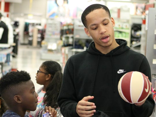 FSU guard CJ Walker signs a basketball Timarrie Stebbins while the two shop for Christmas presents at Target.