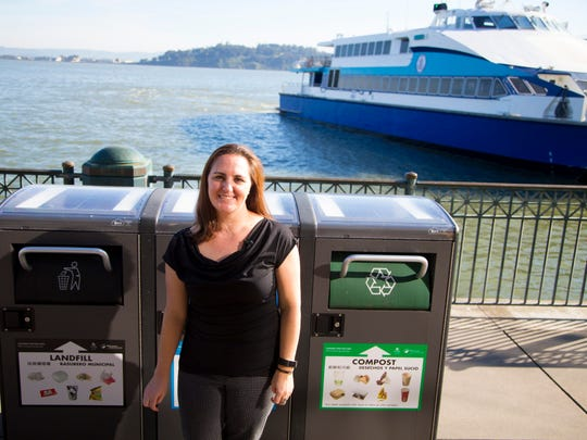 Lauren Sivley, Assistant Property Manager, Equity Office, for the Ferry Building in San Francisco, stands in front of three Bigbelly bins for waste (landfill, recycle, and compost).