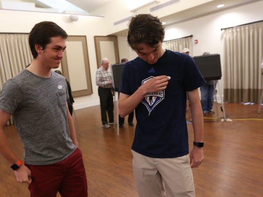 Brothers and first-time voters Carson and Richie Jones vote at the Coxhall and Clay Center 1 voting site in Carmel, put on voting stickers after voting, Tuesday, May 7, 2018. They voted with their brother Garrett and their parents. The Jones brothers are triplets.